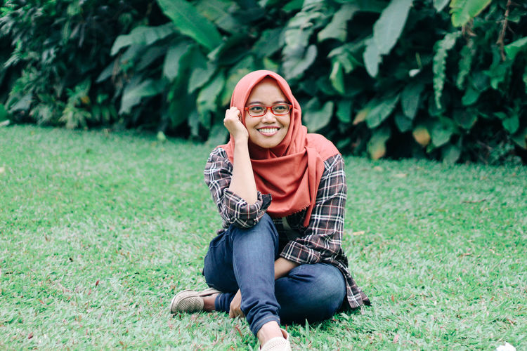 Smiling young woman wearing hijab while sitting on grassy field at park