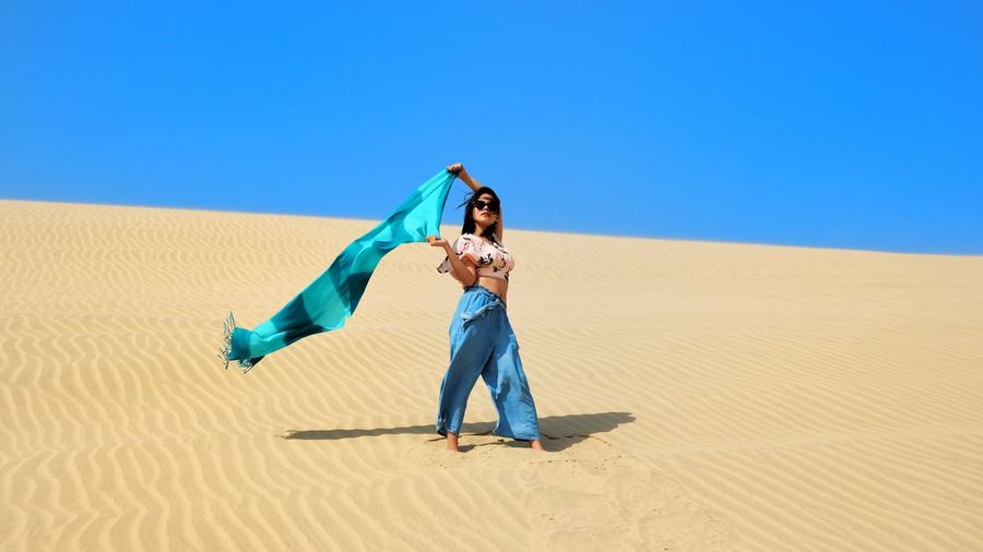 Full length of young woman holding scarf at desert on sunny day