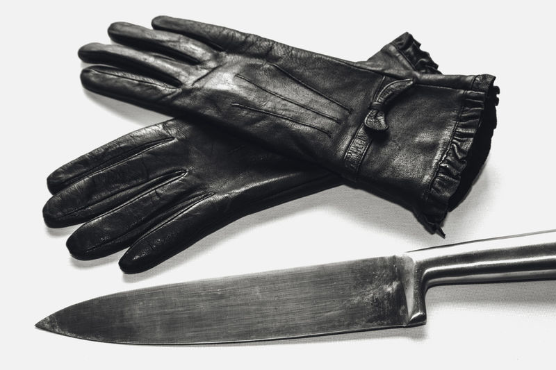 A black and white image of a women's gloves and a butcher knife Crime Forensics Knife Close-up Evidence Gloves Investigation Murder Scenes Murder Weapon No People Still Life Weapon White Background Women