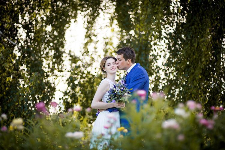 Bridegroom kissing bride on cheek while standing against trees