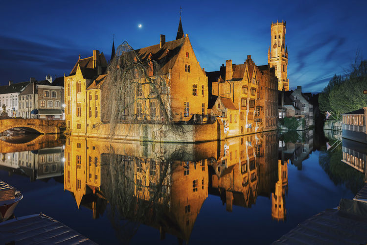 Reflection of illuminated buildings in canal against sky