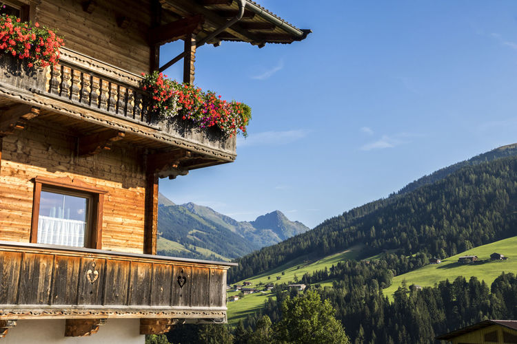 A typical wooden balcony with flowers in Alpbach, a town in western Austria in the state of Tyrol Alpbach Alpbachtal Balcony View Architecture Balcony Beauty In Nature Building Exterior Built Structure Clear Sky Day Flower Flowers Low Angle View Mountain Mountain Range Nature No People Outdoors Scenics Sky Tranquility Window