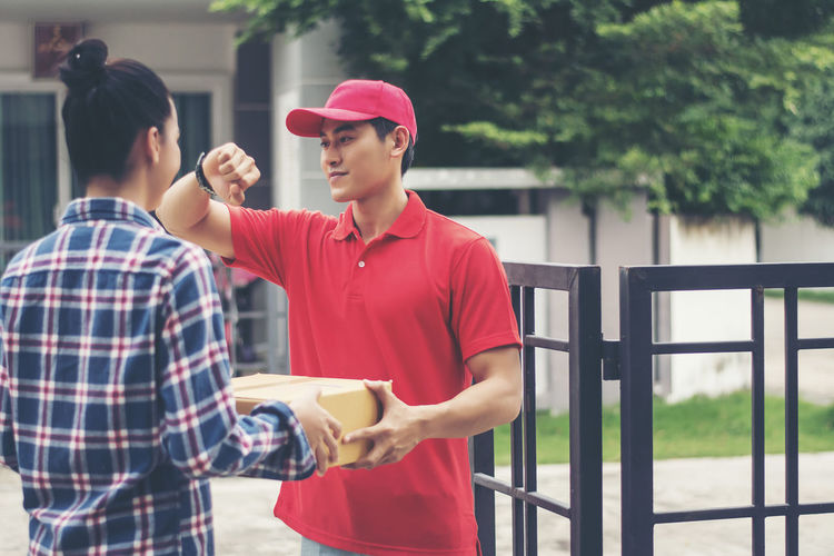 Adult Baseball Cap Cap Casual Clothing Day Focus On Foreground Hat Holding Lifestyles Males  Men Outdoors People Real People Standing Two People Uniform Waist Up Young Adult Young Men