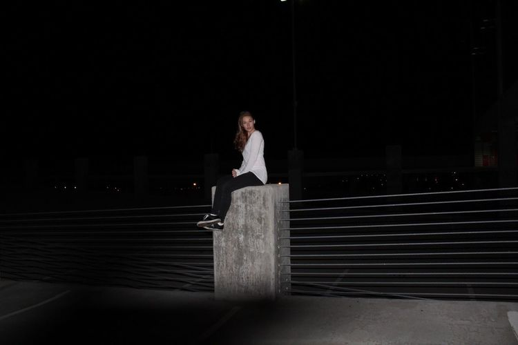 Full length of young woman sitting on concrete structure by railing at night