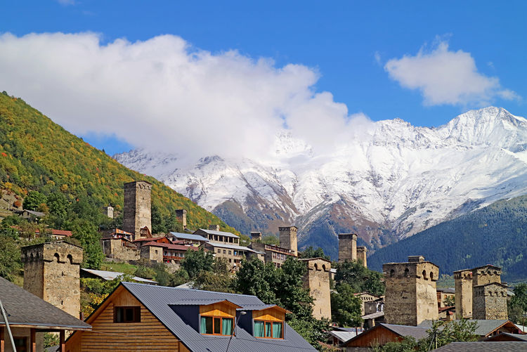 Town by mountains against sky