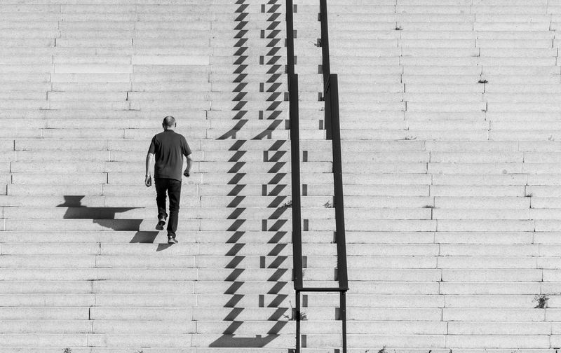 Rear view of man walking on steps during sunny day