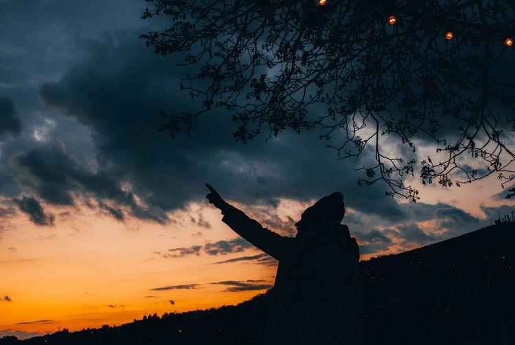 Silhouette person with arms raised against sky during sunset