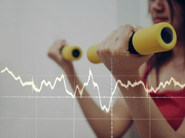 Digital Composite Image Of Pulse Trace Against Mature Woman Exercising At Home