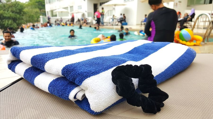 Close-up of towel and hair elastic against people in swimming pool