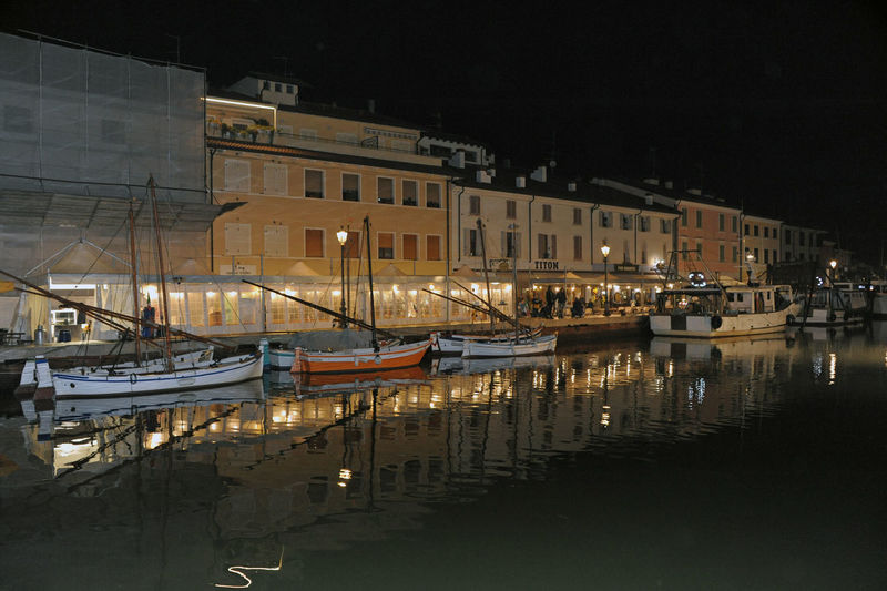 Boats moored at harbor against buildings in city at night