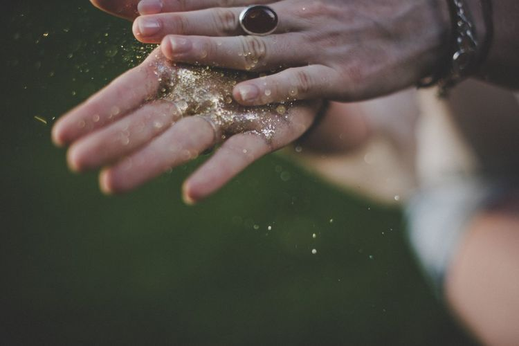 EyeEm Selects Human Hand Real People One Person Glitter Motion Human Body Part Day Holding Lifestyles Outdoors Close-up Spraying Working Freshness People Confetti Gold Shine