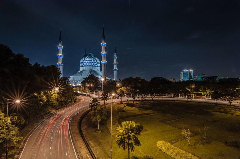 Illuminated sultan salahuddin abdul aziz mosque against sky at night