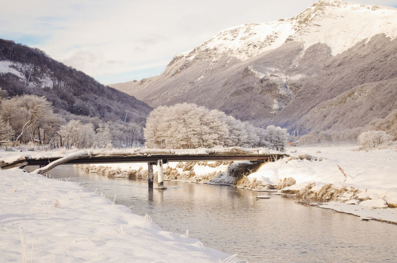 Bridge Over River By Snowcapped Mountain Against Sky