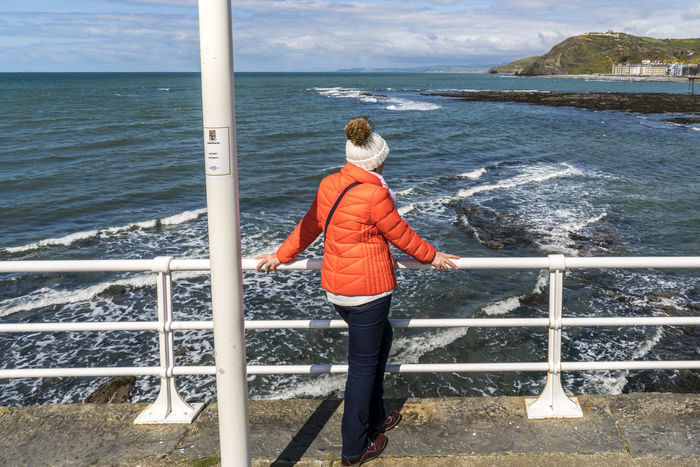 A woman in an orange jacket on the promenade at Aberystwyth, Wales Aberystwyth Contrast Day Full Length One Person Orange Color Outdoors Real People Sea And Sky Seascape Seaside Sky Wales Wales❤ Woman