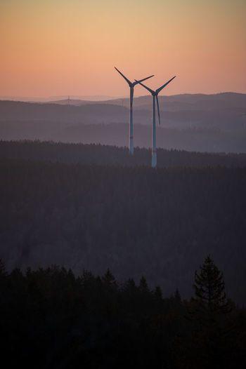 Silhouette wind turbines on land against sky during sunset