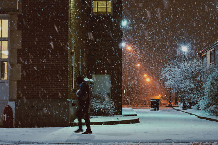 Full length of illuminated street during winter at night