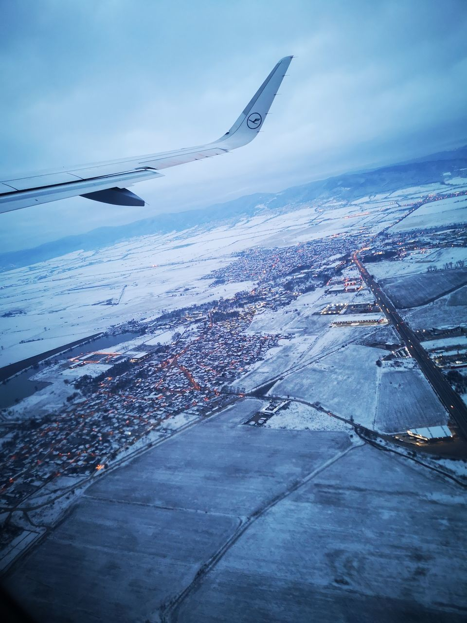 AERIAL VIEW OF AIRPLANE FLYING OVER SEA DURING WINTER