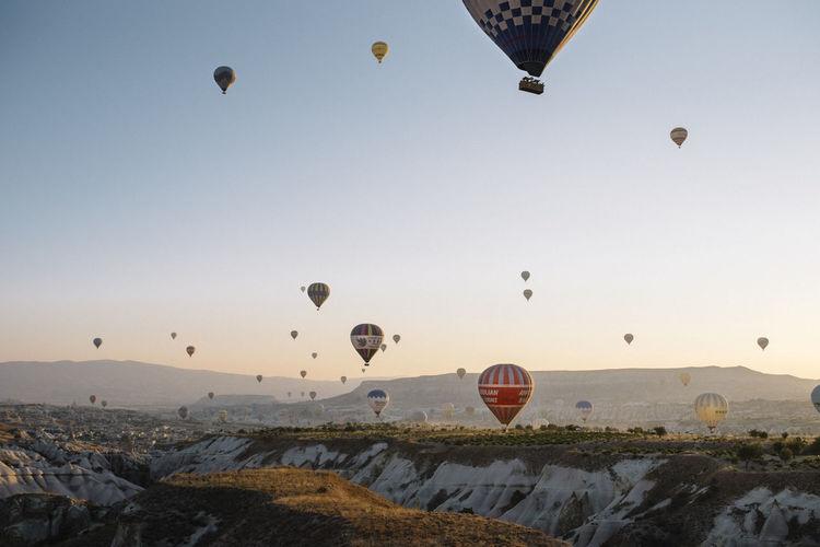 Hot air balloons flying over landscape against sky
