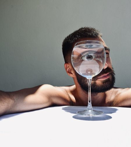 Portrait of young man holding glass against white background
