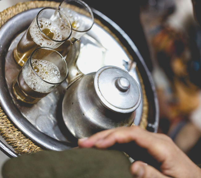 Berber man offers traditional mint tea to guest in Marrakesh, Morroco Arab Berber  Culture Destination Details Glowing Guest Hands Home Integration Little Marrakech Mint Tea Negotiation Pour Selling Service Silver  Sojourn Souks Tea Tin Tradition Travel Tray
