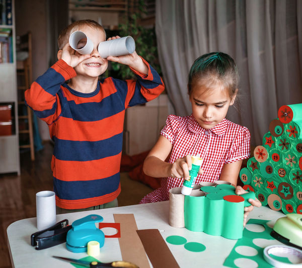 Cute girl and boy preparing christmas decoration at home