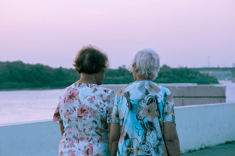 Adult Bonding Casual Clothing Couple - Relationship Emotion Floral Pattern Friendship Leisure Activity Lifestyles Looking At View Love Nature People Positive Emotion Real People Rear View Senior Adult Sky Standing Togetherness Two People Waist Up Women This Is Queer
