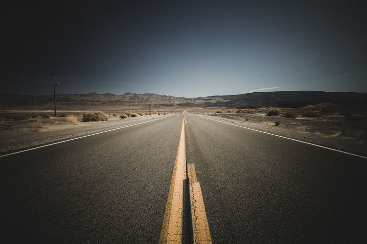 Diminishing perspective of empty road along landscape against clear sky