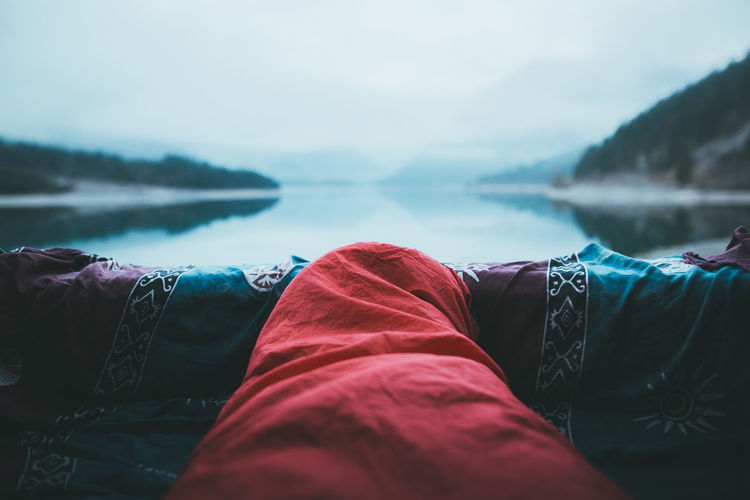 Person wrapped in blanket by lake against sky