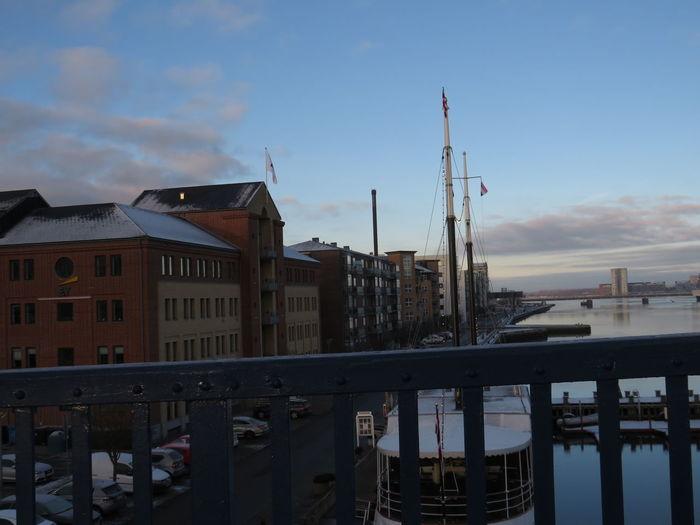 Buildings by pier against sky in city