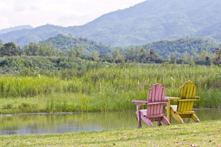 Chair on field by lake