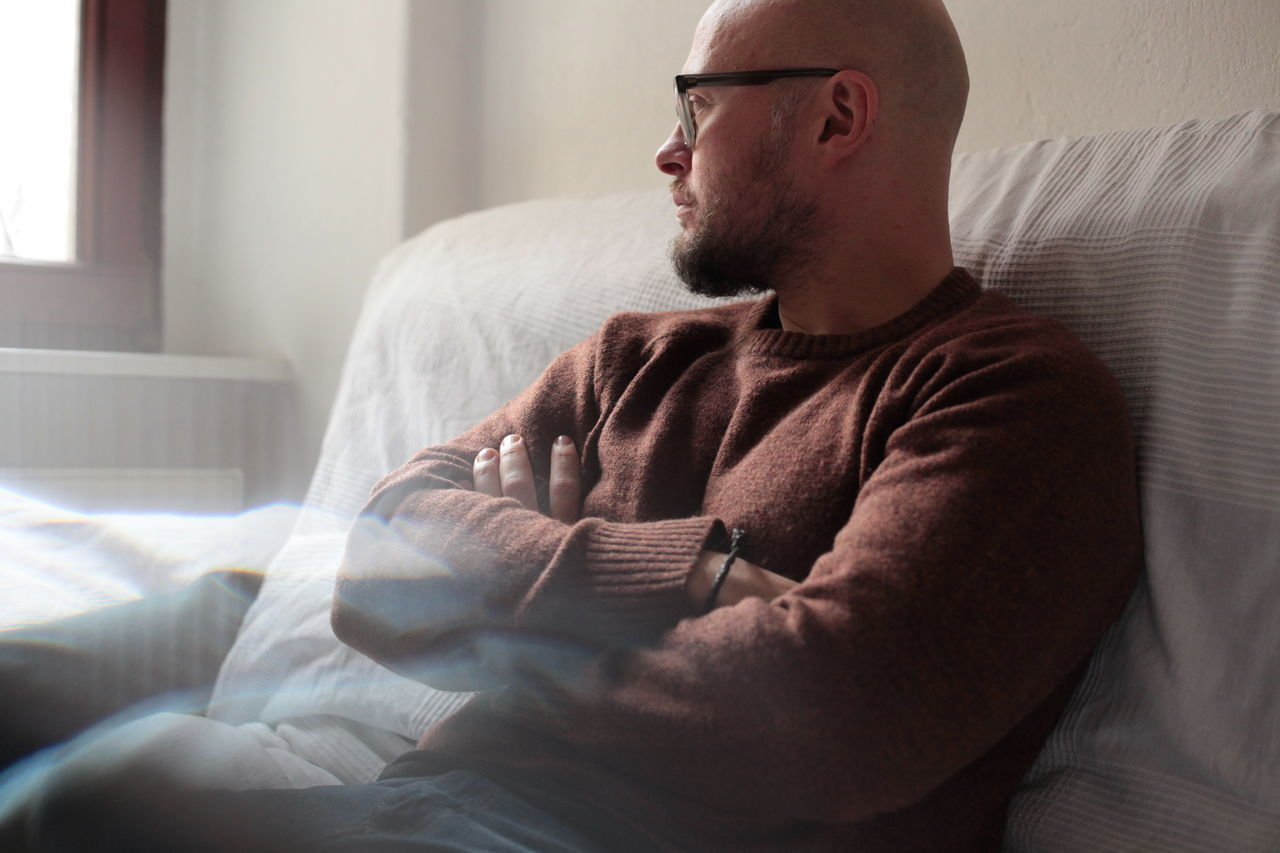 Thoughtful man relaxing on bed at home