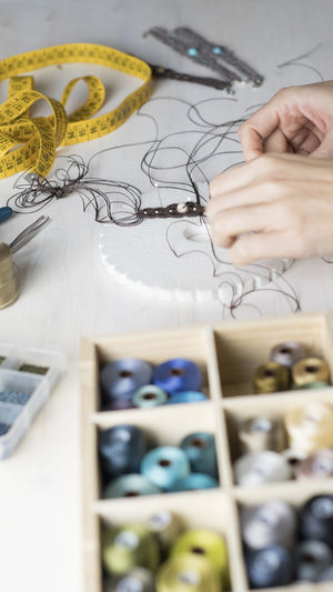 Cropped hands of woman working with thread on table