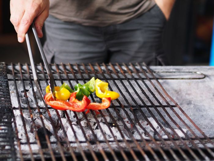 Close-Up Of Man Preparing Bell Peppers On Barbecue Grill