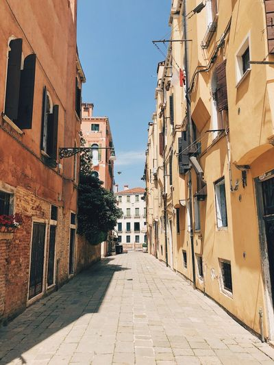 Narrow alley amidst buildings in city during sunny day