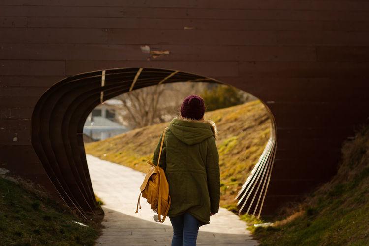Rear view of woman walking towards tunnel