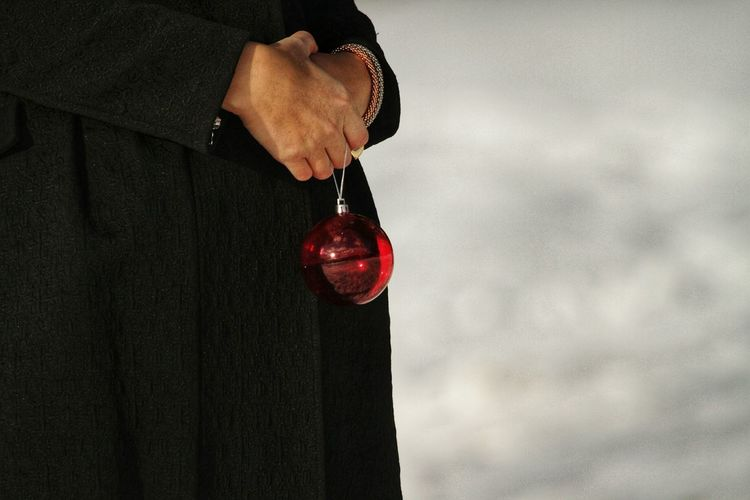 Close-Up Midsection Of Person Holding Red Bauble