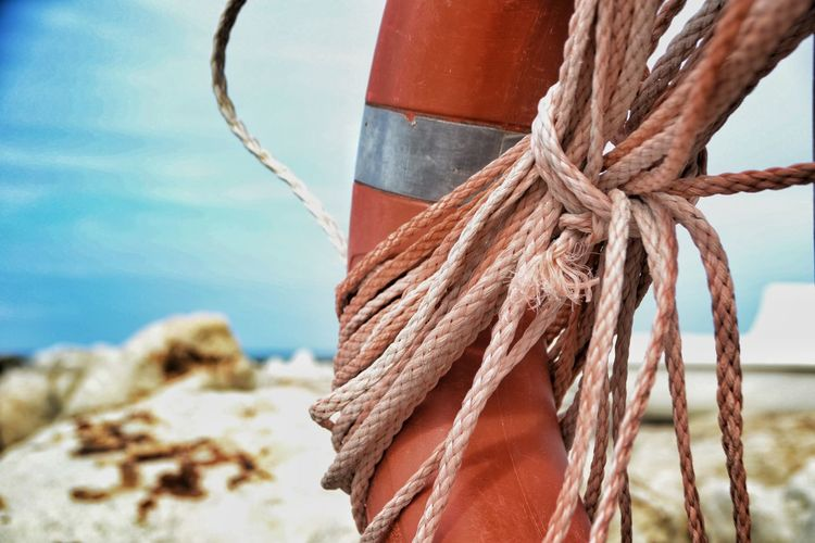 Close-up of rope tied to wooden post in sea