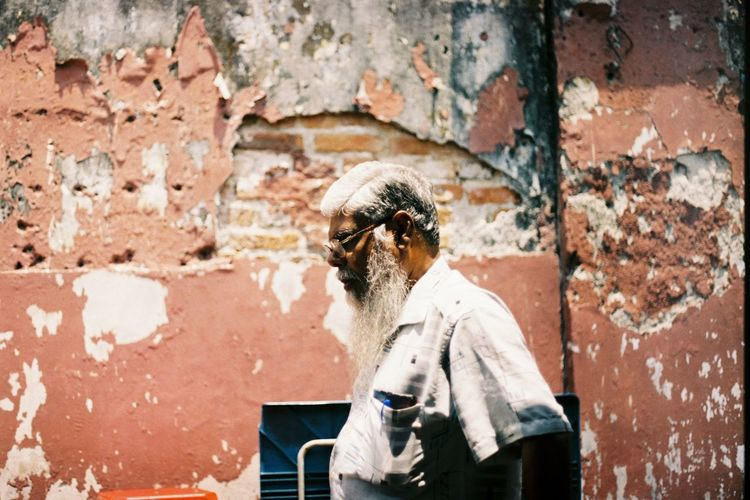 Side View Of Mature Man Standing By Damaged Wall