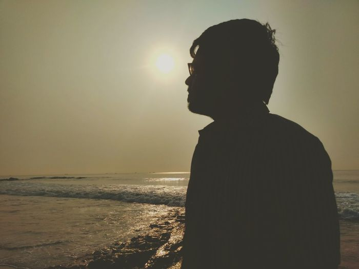 Silhouette of man at beach against sky during sunset