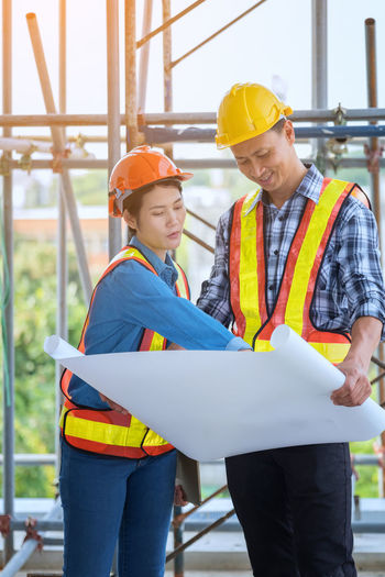 Coworkers with blueprint at construction site