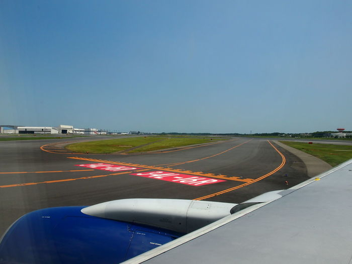 Airplane On Runway Against Clear Blue Sky