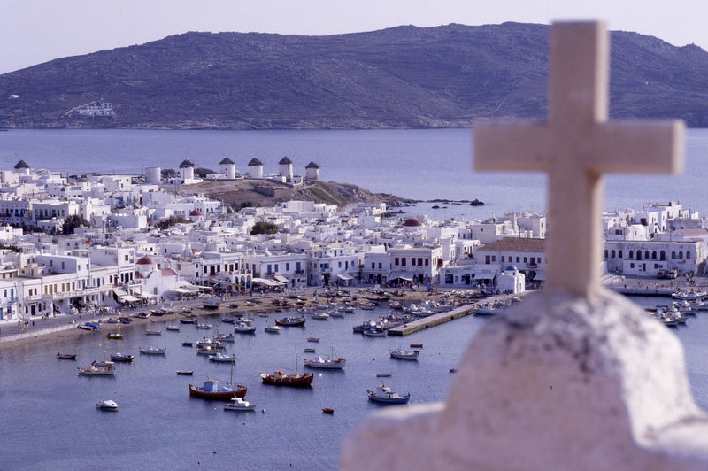 view to the harbour and city Mykonos in Greece Harbor Harbour Myconos Architecture Beauty In Nature Boats Cross Day Greece High Angle View History Island Mountain Mykonos Nature No People Outdoors Religion Scenics Sea Sky Spirituality Travel Destinations Water Wind Mill