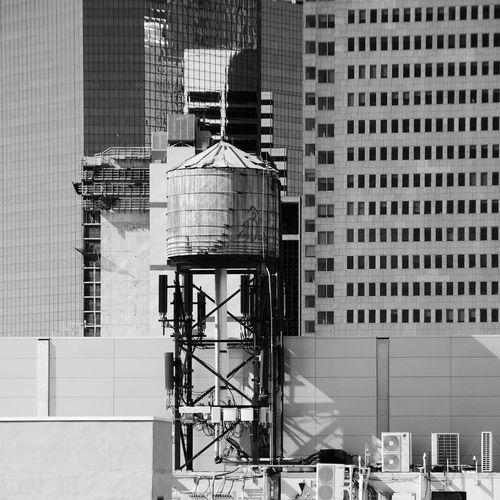 Water tower against modern buildings in city