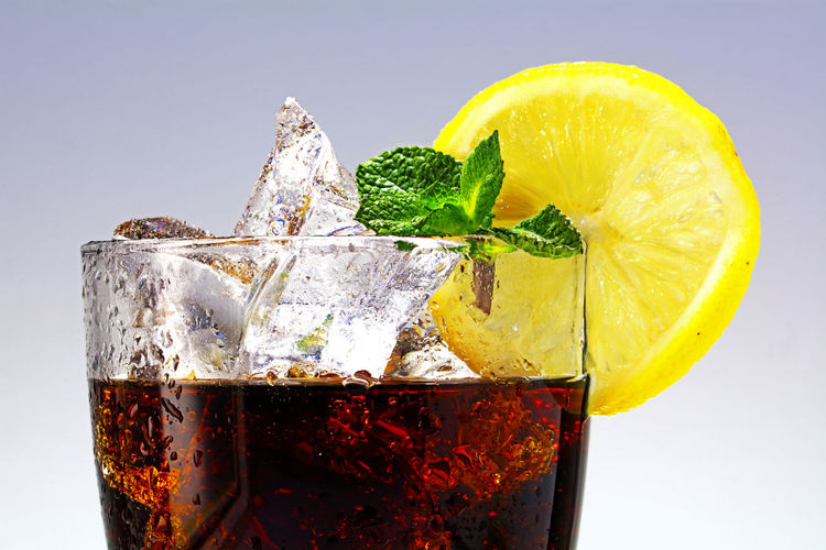 top of a glass of cola or coke with ice cubes, lemon slice and peppermint garnish, closeup with selected focus Icete Bubbles Coke Cola Drink Food Food And Drink Freshness Glass Healthy Eating Ice Lemon No People Refreshment Simplicity SLICE Still Life Table Yellow