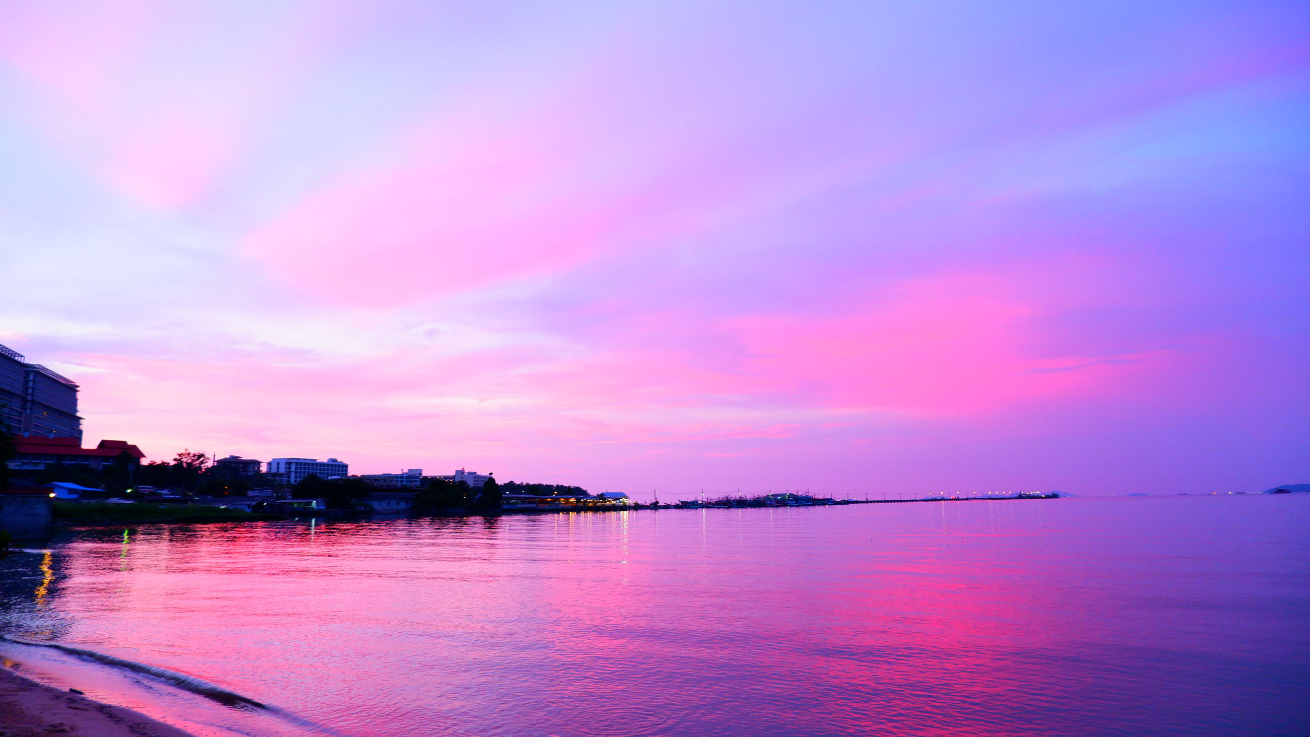 water, sky, sea, sunset, cloud, dawn, beauty in nature, reflection, horizon, scenics - nature, nature, tranquility, architecture, pink, afterglow, evening, no people, tranquil scene, travel destinations, purple, multi colored, ocean, built structure, outdoors, beach, city, landscape, dramatic sky, idyllic, land, magenta, travel, building exterior, environment, blue, building
