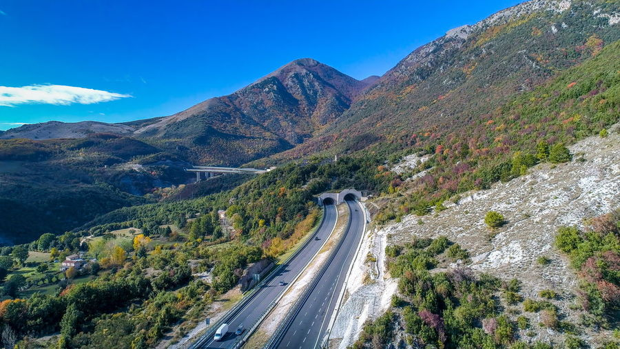 High angle view of road amidst mountains against blue sky