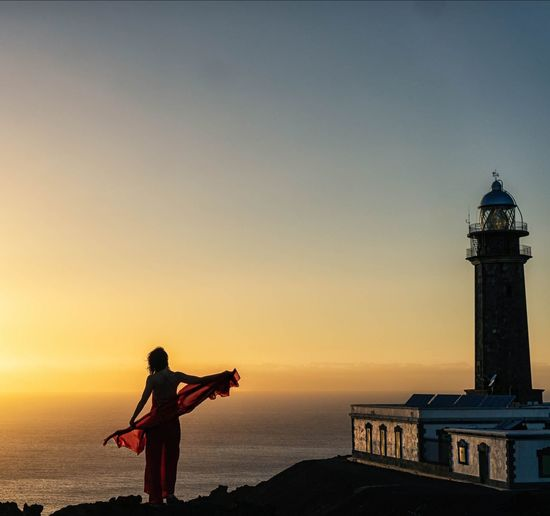 Silhouette woman standing on cliff by lighthouse against sea at sunset