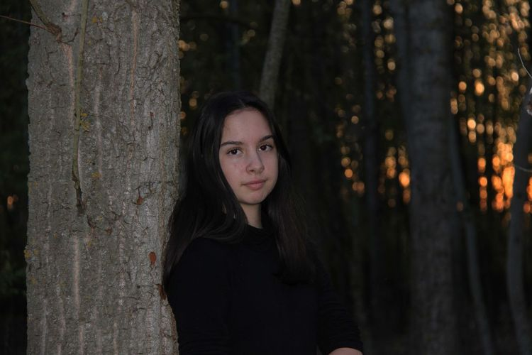 Portrait of girl against tree trunk in forest