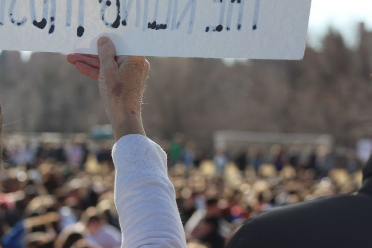 Cropped hand holding banner with text during protest