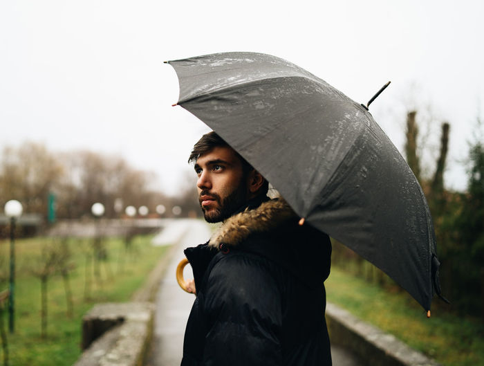 Side view of young man holding umbrella while standing outdoors during rainy season